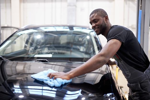 Homem afro-americano, mecânico de automóveis limpa a superfície perfeita da máquina após o polimento