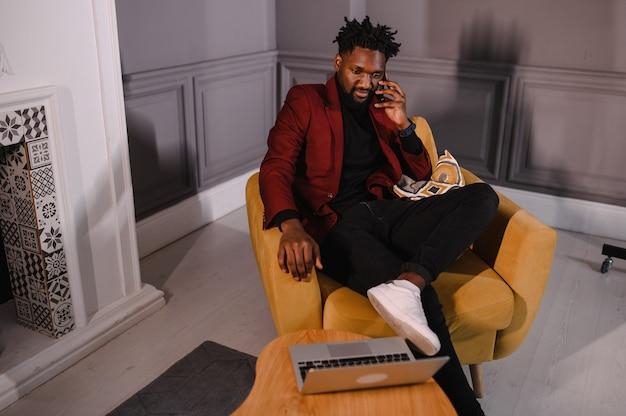 Homem afro-americano milenar sorridente, trabalhando com aplicativos ou se comunicando on-line no laptop
