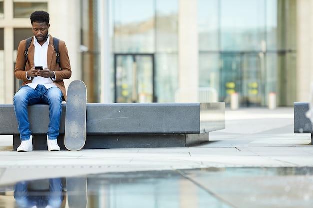 Homem afro-americano moderno usando smartphone na cidade