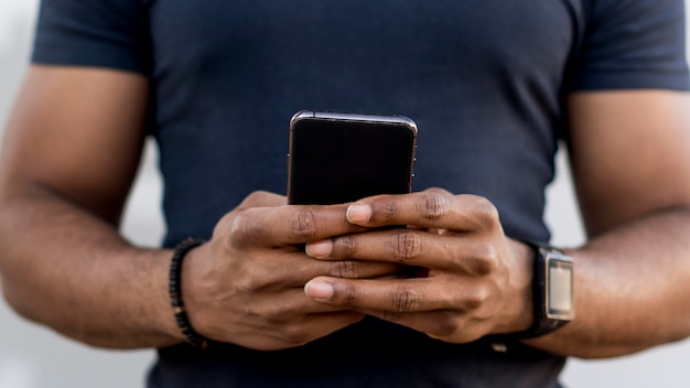 Homem afro-americano moderno verificando o telefone