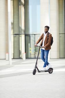 Homem afro-americano, montando scooter elétrico, em, cidade