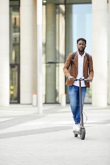 Homem afro-americano, montando scooter elétrico