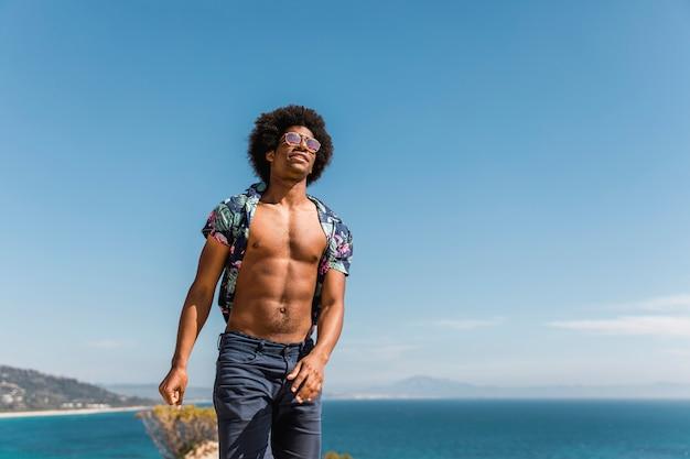 Homem afro-americano muscular considerável que levanta no fundo azul do céu e do mar