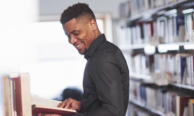 Homem afro-americano na biblioteca procurando informações nos livros