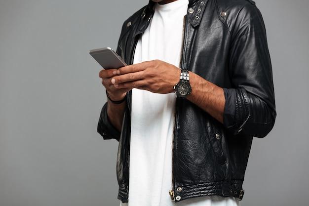Homem afro-americano na jaqueta de couro com smartphone