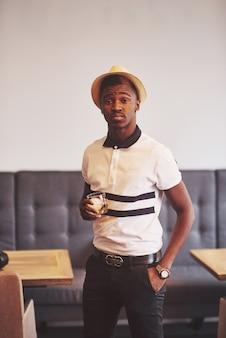 Homem afro-americano na moda no chapéu com copo de uísque
