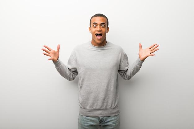 Homem afro-americano no fundo da parede branca com surpresa e expressão facial chocada
