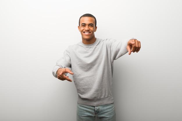 Homem afro-americano no fundo de parede branca aponta o dedo para você enquanto sorrindo