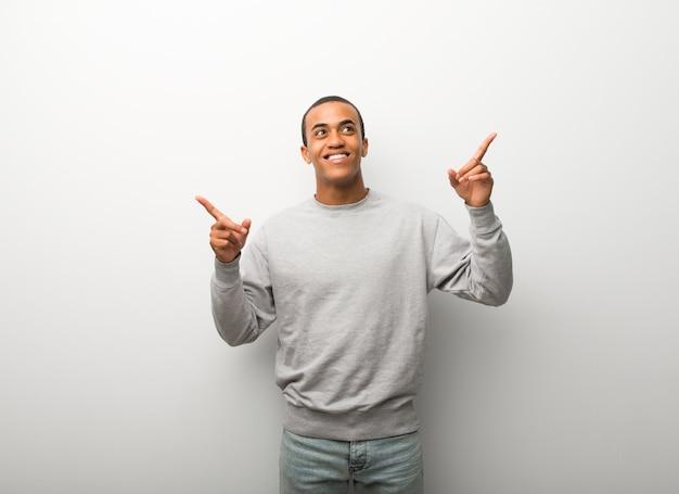 Homem afro-americano no fundo de parede branca, apontando com o dedo indicador uma ótima idéia