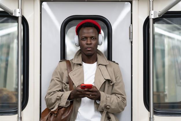 Homem afro-americano no trem do metrô usando telefone celular ouve música com fones de ouvido sem fio