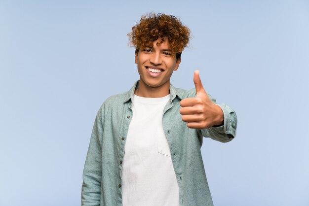Homem afro-americano novo com polegares acima porque algo bom aconteceu