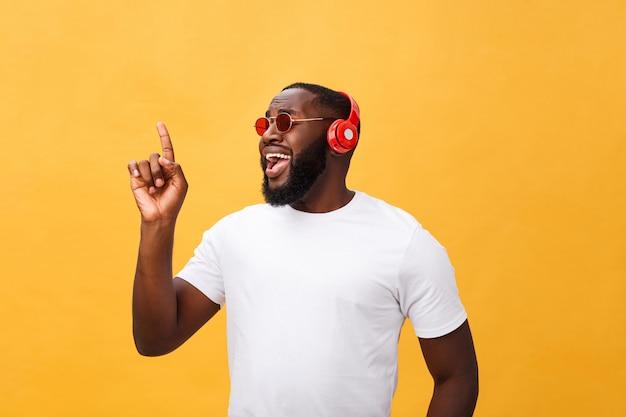 Homem afro-americano novo considerável que escuta e que sorri com música em seu dispositivo móvel. isolado sobre o fundo amarelo.