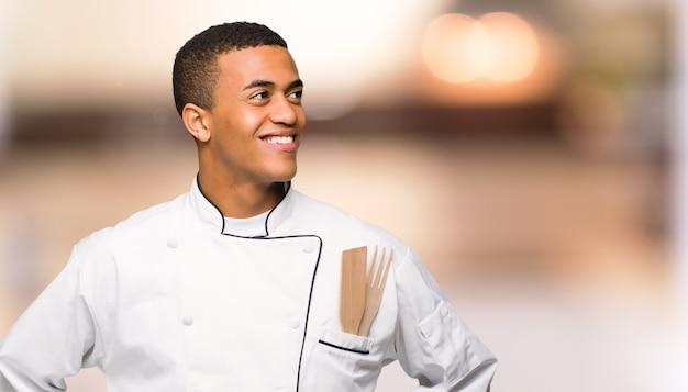 Homem afro-americano novo do cozinheiro chefe que levanta com os braços no quadril e que ri em fundo unfocused