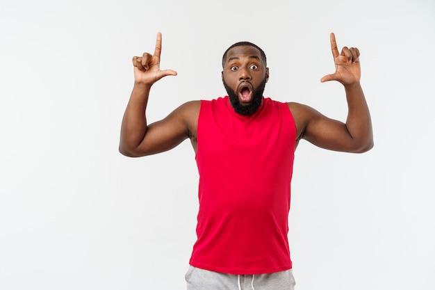 Homem afro-americano novo do esporte que aponta o dedo com surpreendido, sente-se bem sucedido e próspero