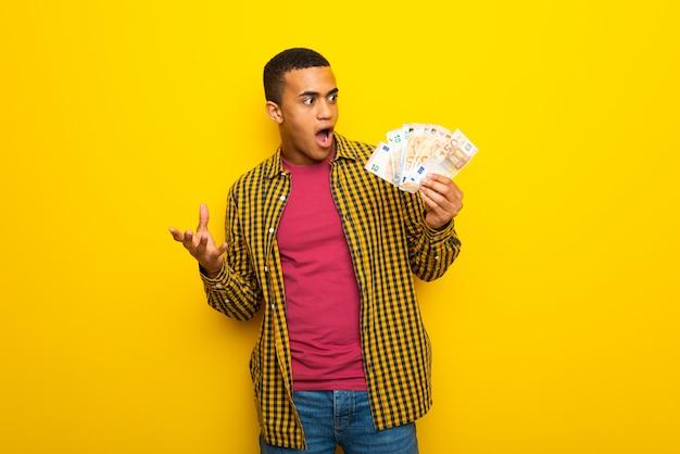 Homem afro-americano novo no fundo amarelo que toma muito dinheiro