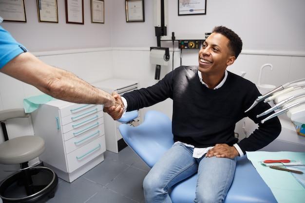 Homem afro-americano novo que agita a mão do dentista da colheita que tem a visita na clínica médica.