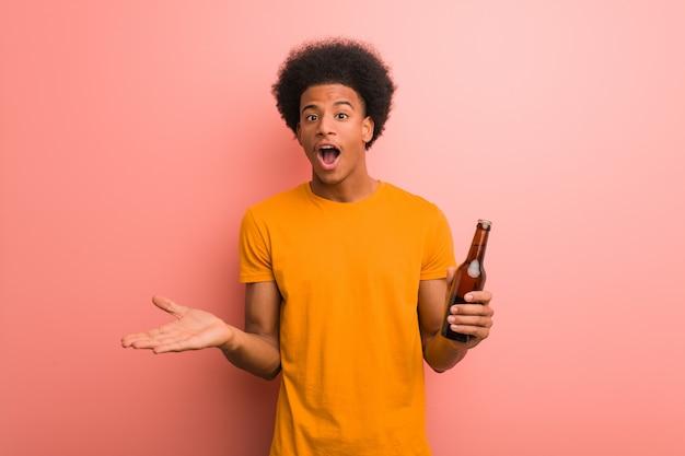 Homem afro-americano novo que guarda uma cerveja que comemora uma vitória ou um sucesso