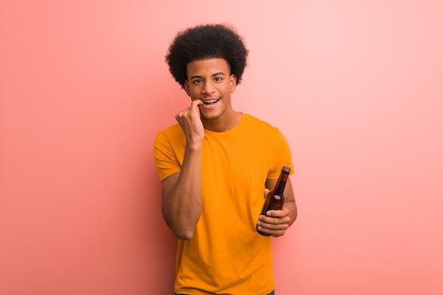 Homem afro-americano novo que guarda uma cerveja que morde pregos, nervoso e muito ansioso