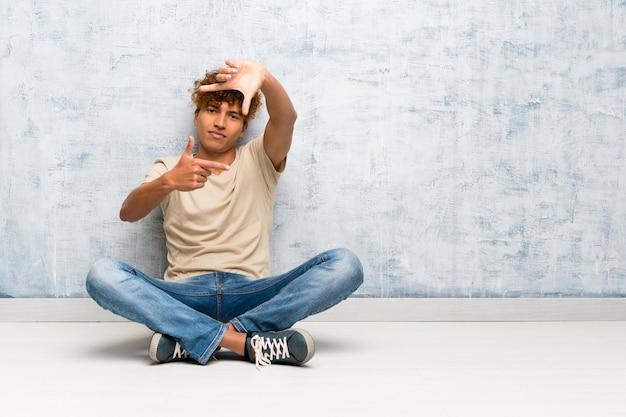 Homem afro-americano novo que senta-se na cara de focalização do assoalho. símbolo de enquadramento