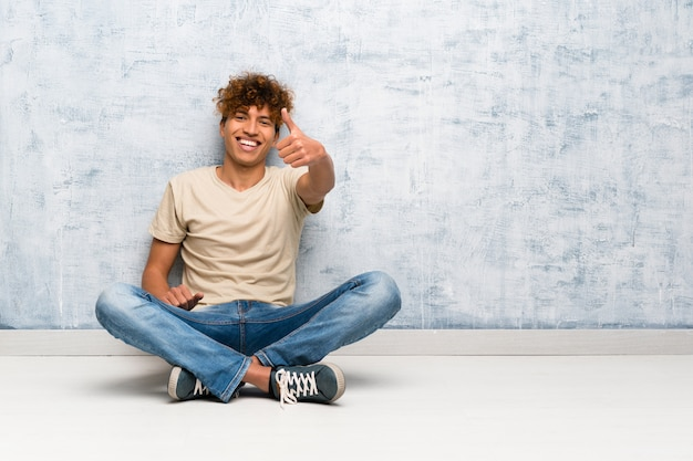 Homem afro-americano novo que senta-se no assoalho com polegares acima porque algo bom aconteceu