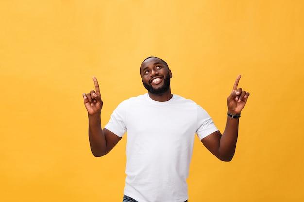 Homem afro-americano novo sobre o fundo amarelo que aponta para cima
