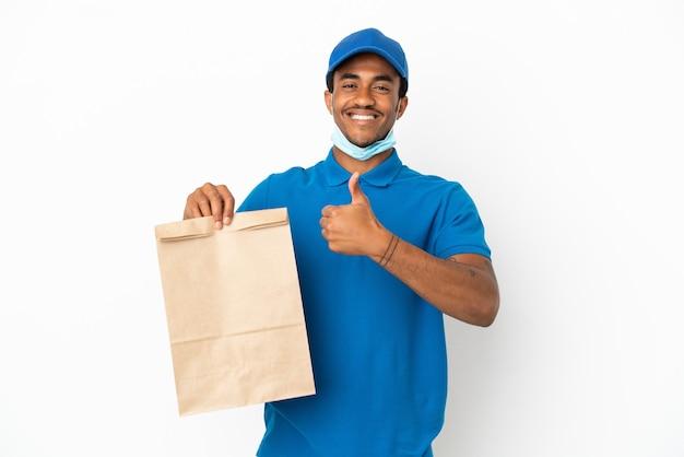 Homem afro-americano pegando uma sacola de comida para viagem isolada no fundo branco e fazendo um gesto de polegar para cima