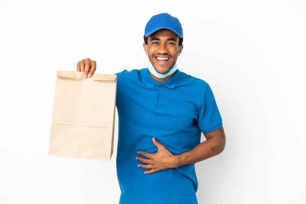 Homem afro-americano pegando uma sacola de comida para viagem isolada no fundo branco e sorrindo muito