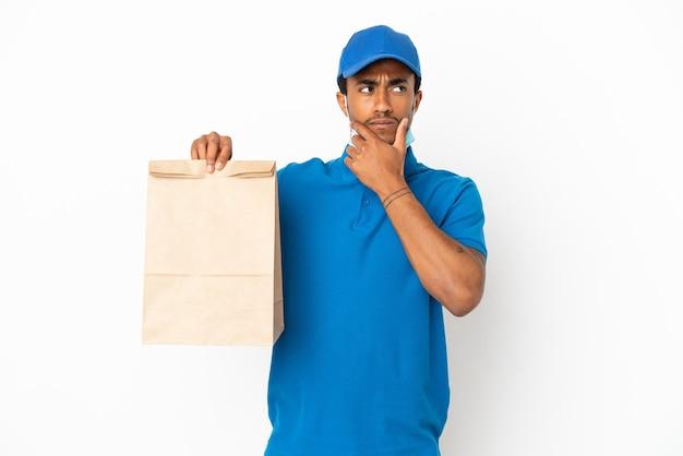 Homem afro-americano pegando uma sacola de comida para viagem isolada no fundo branco, tendo dúvidas e pensando