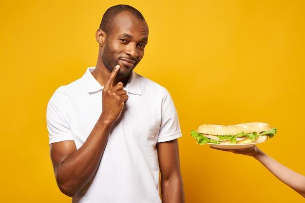 Homem afro-americano pensa em comer sanduíche.