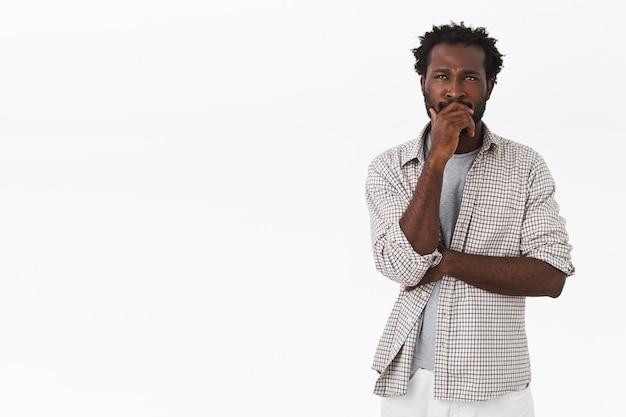 Homem afro-americano pensativo e inseguro, pensativo, tocando a barba, franzindo a testa e olhando para cima