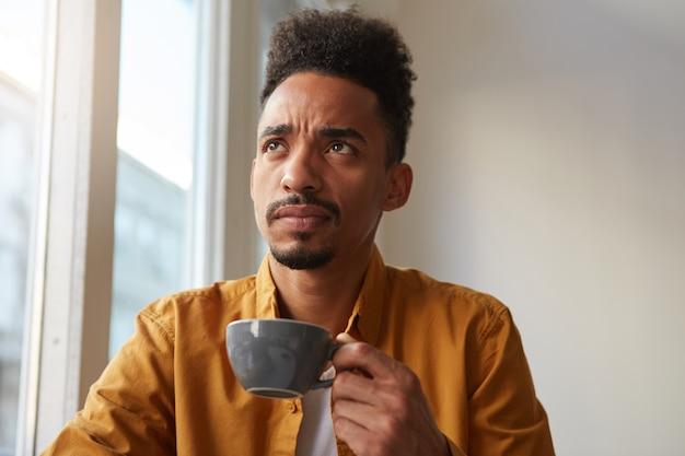 Homem afro-americano perplexo, veste camisa amarela, senta-se à mesa de um café e bebe café, lembra se o ferro desligou antes de sair do apartamento. olhando pensativamente para a distância.