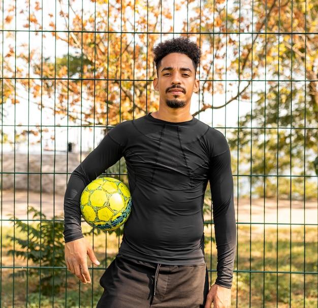 Homem afro-americano posando com uma bola de futebol ao ar livre
