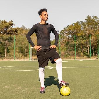 Homem afro-americano posando com uma bola de futebol do lado de fora