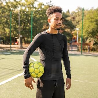 Homem afro-americano posando com uma bola de futebol em um campo