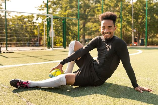 Homem afro-americano posando com uma bola de futebol