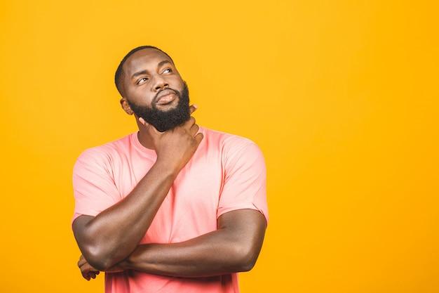 Homem afro-americano preto de pensamento com a expressão séria que olha, levantando isolado contra a parede amarela.