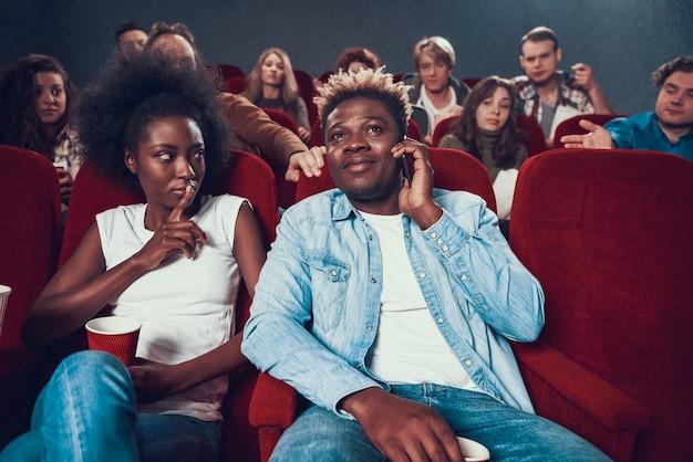 Homem afro-americano que fala no telefone durante a mostra de filme.