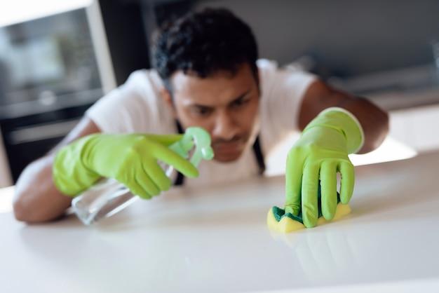 Homem afro-americano que limpa na cozinha.