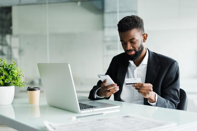Homem afro-americano que paga com cartão de crédito on-line ao fazer pedidos via internet móvel, fazendo transações usando o aplicativo do banco móvel.