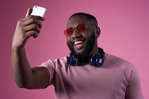 Homem afro-americano que toma o selfie isolado.