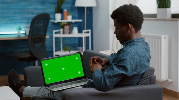 Homem afro-americano que trabalha com chroma key isolado laptop exibir tela verde mock up mockup com.