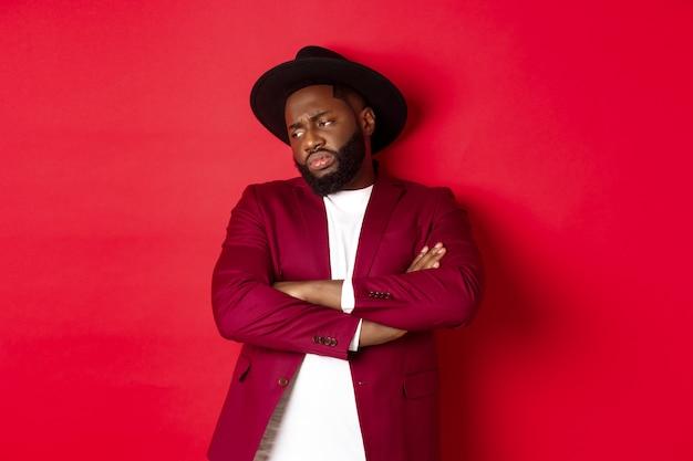 Homem afro-americano relutante e chateado olhando para longe, braços cruzados no peito ofendido, angustiado de pé contra um fundo vermelho