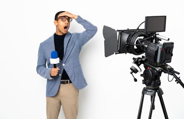 Homem afro-americano repórter segurando um microfone e relatando notícias em branco isolado fazendo gesto de surpresa enquanto olha para o lado