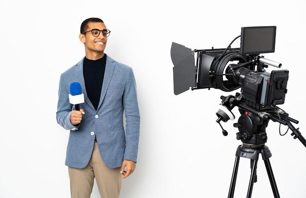 Homem afro-americano repórter segurando um microfone e relatando notícias em branco isolado, olhando para o lado e sorrindo