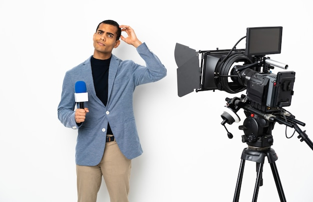 Homem afro-americano repórter segurando um microfone e relatando notícias sobre fundo branco isolado tendo dúvidas