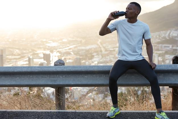 Homem afro-americano sedento bebe água doce, aproveita o intervalo após os treinamentos esportivos ao ar livre, senta-se em uma placa de estrada com uma cópia da vista panorâmica da montanha para conteúdo promocional ou informações