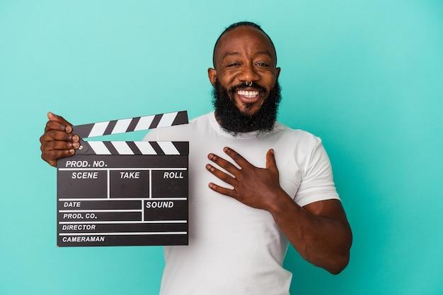 Homem afro-americano segurando claquete isolada na parede azul ri alto, mantendo a mão no peito.