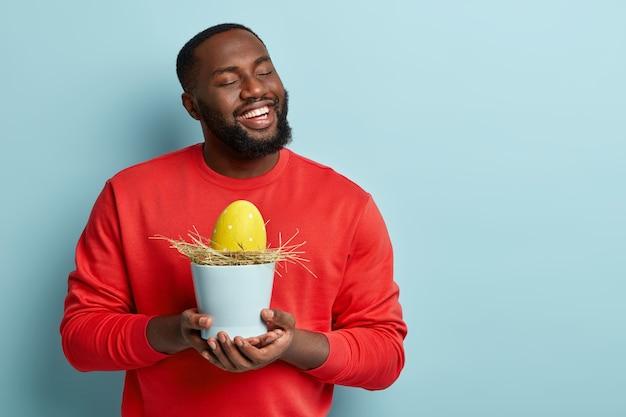 Homem afro-americano segurando ovo de páscoa