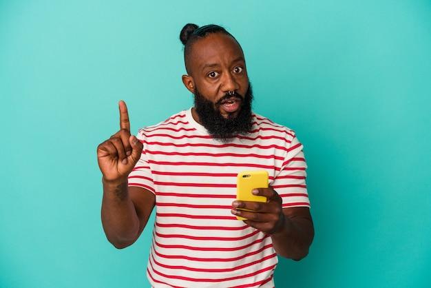 Homem afro-americano segurando um telefone celular isolado em um fundo azul