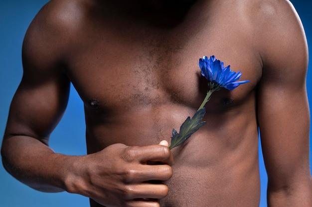 Homem afro-americano segurando uma flor azul